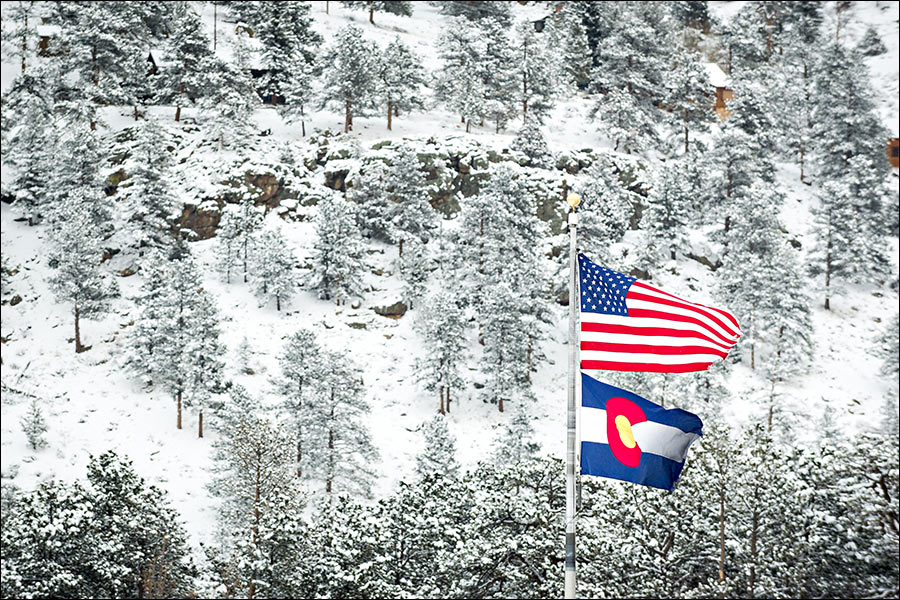 Colorado State flag and U.S. flag in the snow