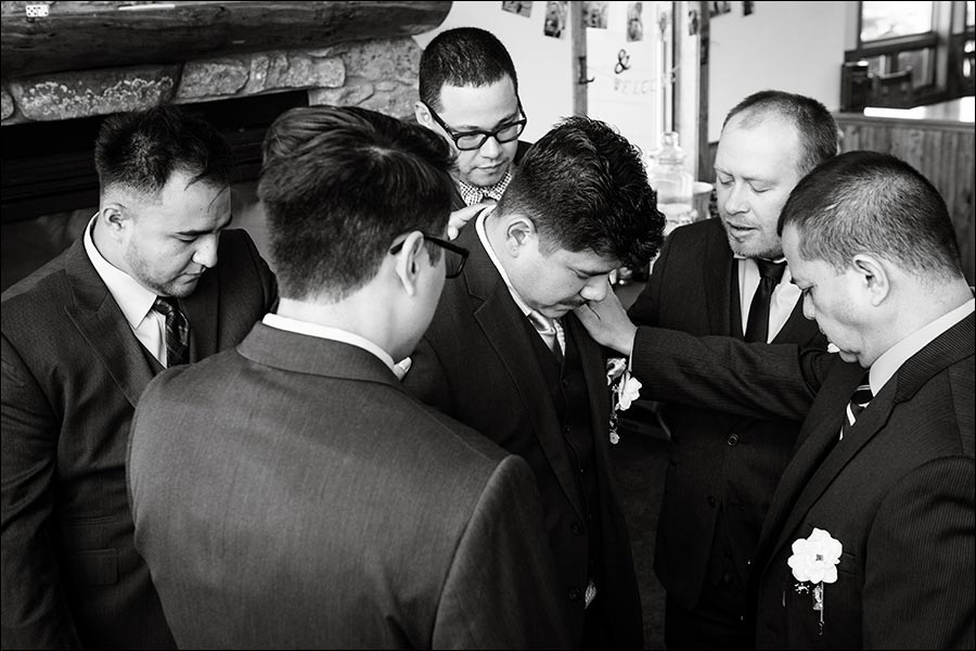 Photo of the groomsmen praying before the wedding